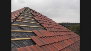 image of tile roofing being installed